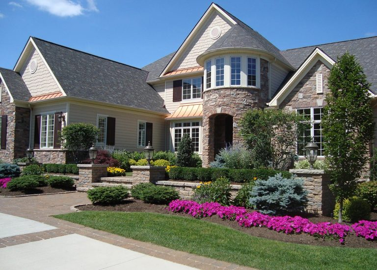 exterior landscaping with bright purple flowers designed by The Bremec Group