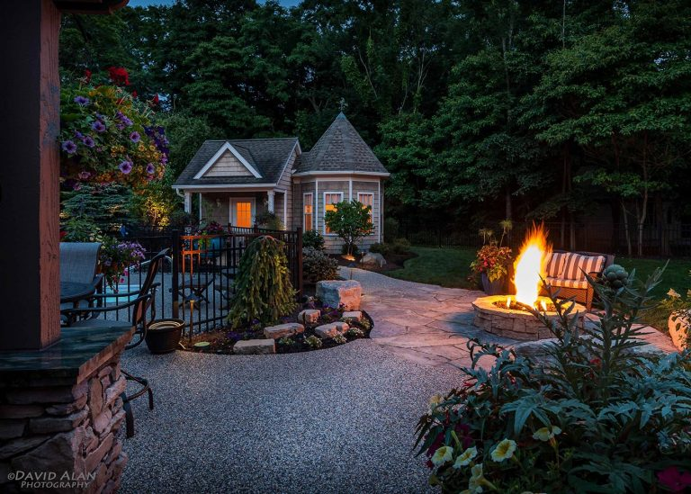 nighttime view of outdoor patio and fire pit with fire designed by The Bremec Group