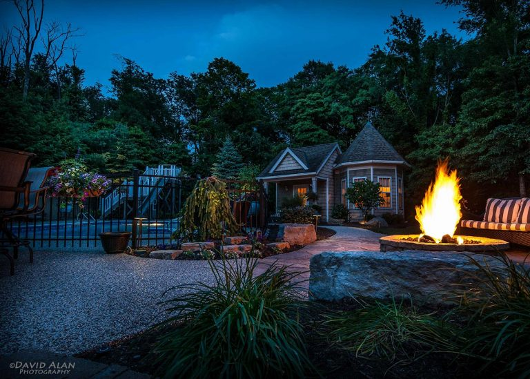 nighttime view of outdoor landscape with fire pit designed by The Bremec Group